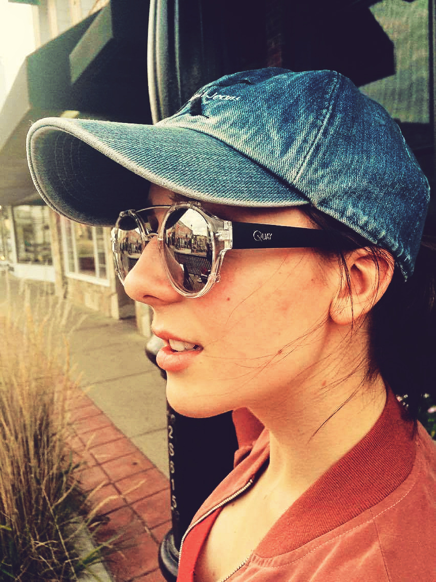 blue jeans ball cap, round sunglasses and red shirt collar , pretty girl in Medicine Hat Alberta