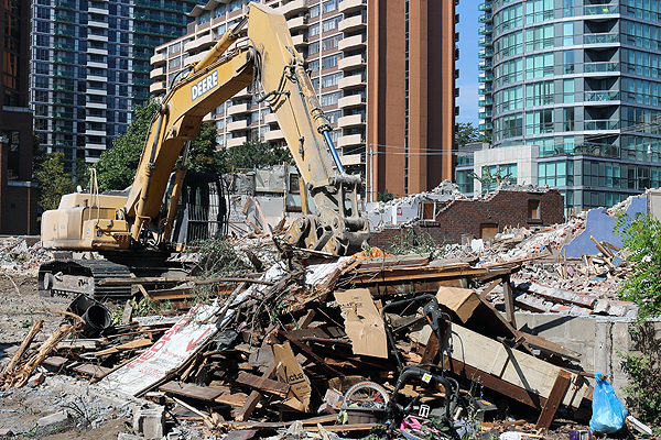 AFTERMATH: An excavator sits idle after demolishing a row of single-family dwellings along the southwest corner of Redpath and Roehampton.