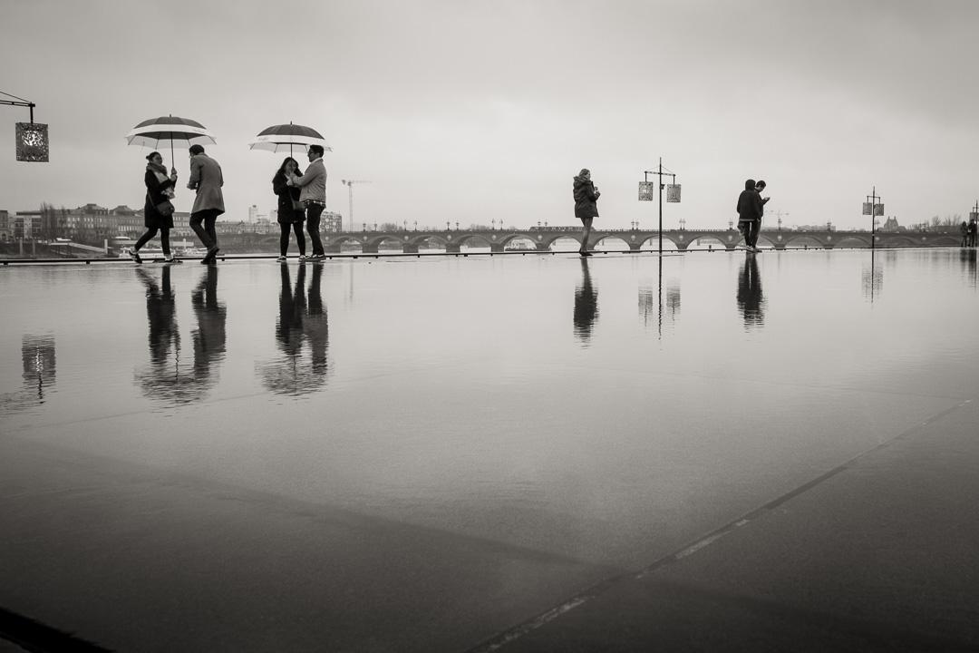 Des couples s'abritent sous des parapluies identiques. Ils font un ballet au miroir d'eau.
