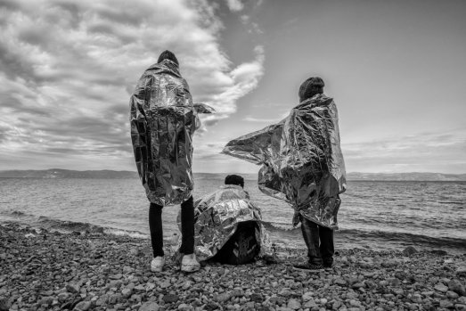 Three men covered in thermal blankets shortly after their arrival on the shores of Lesvos. All three take a moment and look on towards the Turkish coast, where they came from.