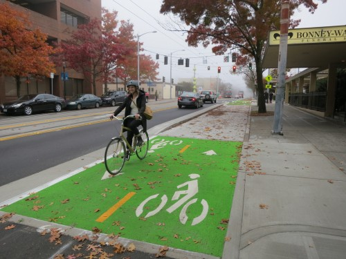 Woman riding on a two-way protected bike lane, not dying. [by Seattle DOT]