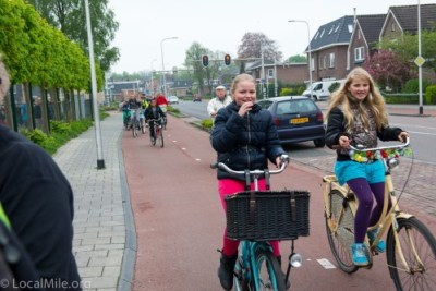 Being able to socialize while riding is a critical element in Dutch cycleway design. This cycletrack is safe for people of all ages and designed so that two people (or three) may ride side-by-side and still allow room for others to pass (as we can see from the gentleman behind these students).