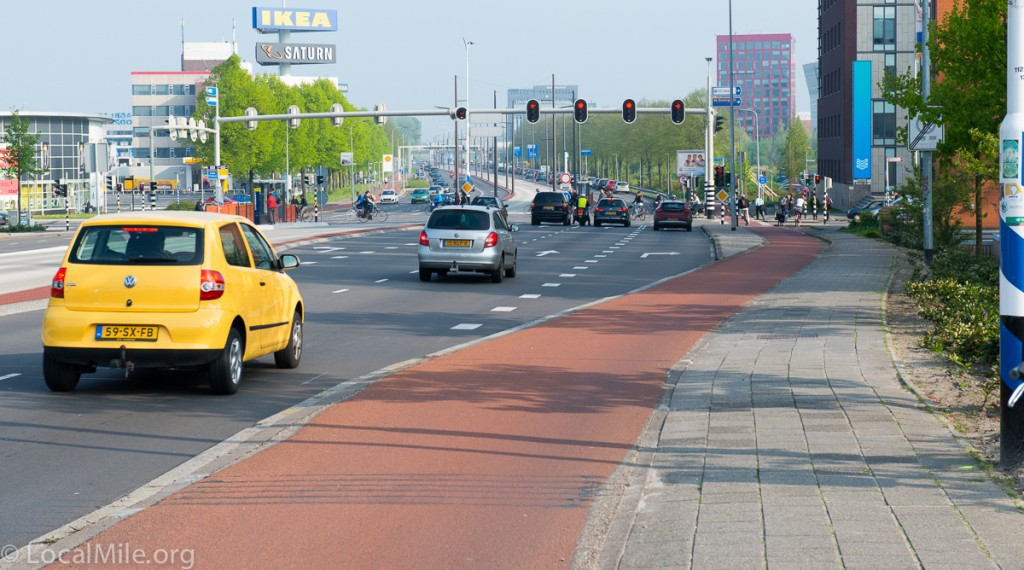 The junction ahead uses simultaneous green for bicycle riders and disabled. It has proven very safe and efficient even for this large of an intersection. Note how the bicycle path veers away from the junction so that when bicycle riders are crossing that drivers (turning right from this view) will be more able to see them.