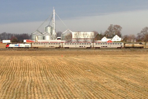 Amtrak train passing a farm