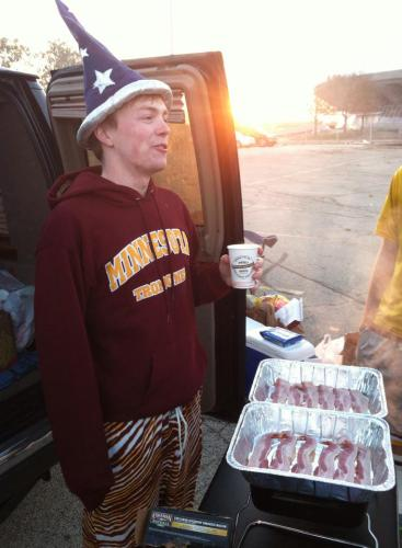 This is me, with a wizard hat and Zubaz, standing near an SUV and two trays of bacon, while situated on a surface parking lot. It is actually nega-me.