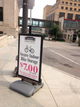 "A sign advertises ""Secure Indoor Bike Storage, seven dollars per month"" outside of the Union Depot in downtown Saint Paul. The sign is placed on a street corner, and the photo is directed out into the street, which is crossed by a skyway about a block down."
