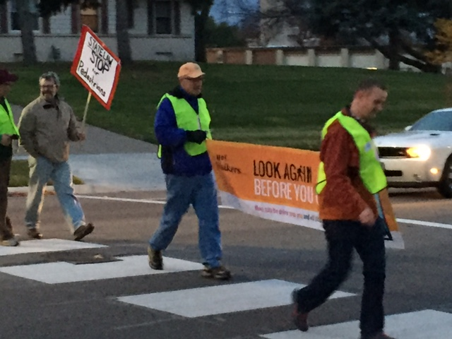 Volunteers cross the street with signs