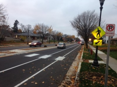 """The photo shows a continental style crosswalk from one side of the road to a median. A sign in the foreground reads """"No Parking Begins"""" beyond that sign is a crosswalk pedestrian sign, a firehydrant and finally a sign which reads """"No Parking Ends"""", but is illegible at this distance with this camera."""