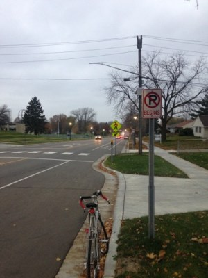 """In the foreground a """"No Parking Begins"""" sign is in front of a driveway, immediately after the driveway the curb juts out into the street about 5-6 feet, meets a crosswalk, and returns to its original line at the next driveway."""
