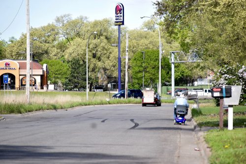 Photo of street with person in motorized scooter and no sidewalk