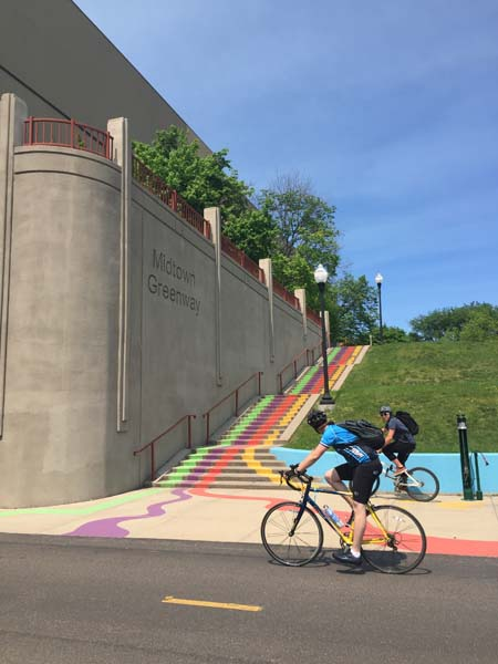 Cyclists on the Midtown Greenway near painted stairs leading to Chicago Avenue S