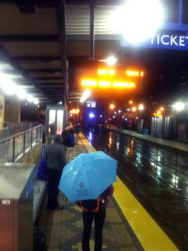 Photo of Green Line light rail platform in rain at night