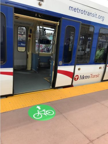 Green circles with bicycles on light rail station platforms show which doors to use to board with bikes