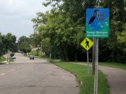 Stillwater Ave from the east: riders are greeted with a watershed district and pedestrian crossing sign.