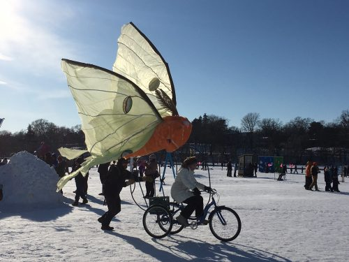 Bicycle with large butterfly wings being ridden on a frozen lake on a sunny day
