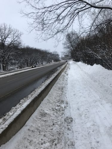 Clear road next to fully snow covered bike path