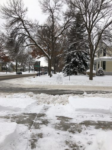 Photo of a sidewalk with a foot-high snow bank blocking access