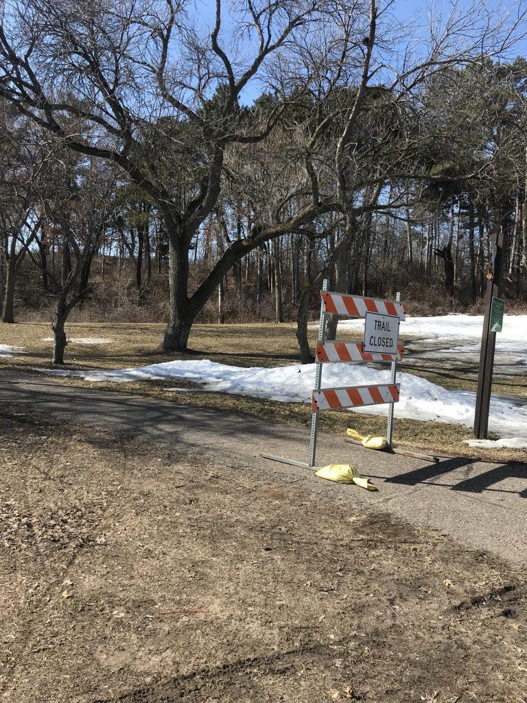 """Trail closed"" sign blocking path"