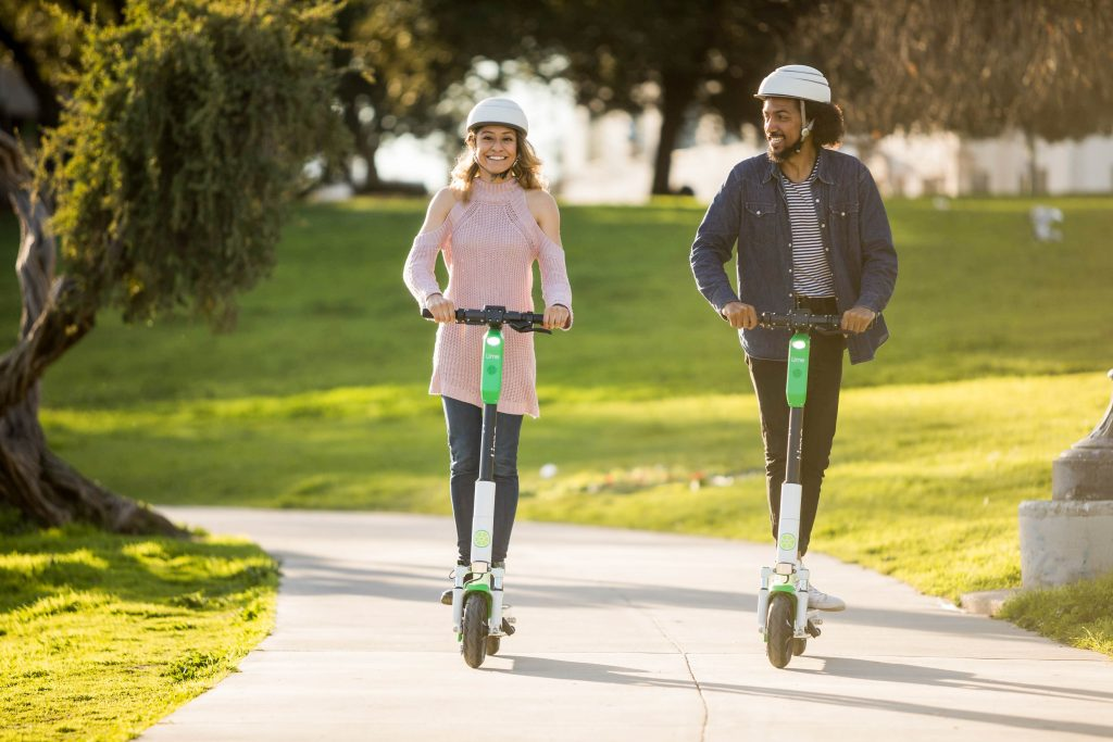 Two Lime riders riding scooters down a park sidewalk