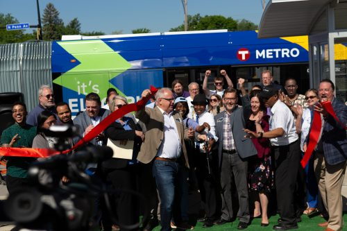Governor Walz grabs a freshly cut ribbon to celebrate the successful ribbon-cutting of Metro Transit's C Line. The C Line operates between Downtown Minneapolis and Brooklyn Center, paralleling Metro Transit's Route 19.