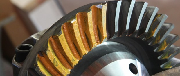 Next a section of 5 or 6 teeth get painted with yellow grease and the ring gear rotated several revolutions. This transfer the contact pattern for the gears. If the pinion gear is too deep, the gears will grind, too shallow and you don't have enough contact area. Either situation will greatly reduce the life of the gears. This pattern shown here is too close.