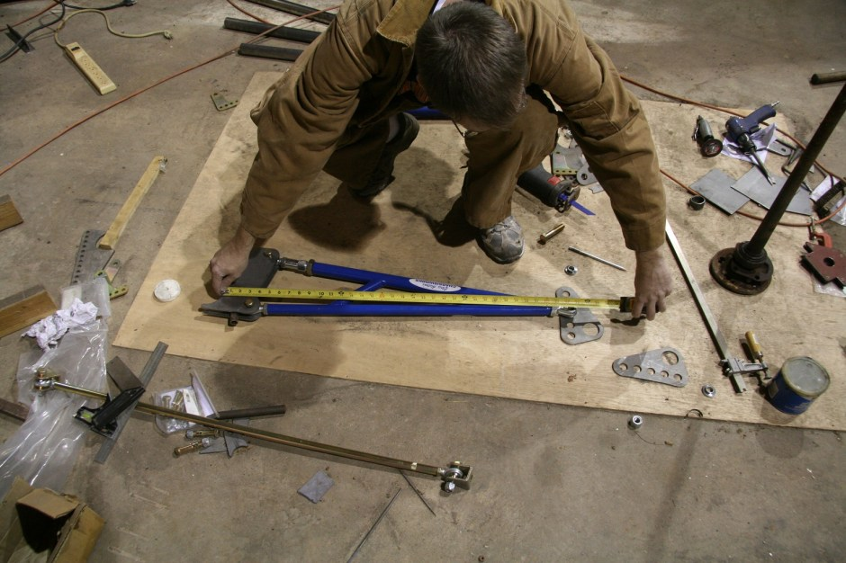 We used a sheet of plywood on the floor to set up the bars. We squared the bars 90-degrees to the vertical center of the rear diff mounting point and measured the actual length of the bars. This is an important step in assuring the bars are located front to back in the wheel well.