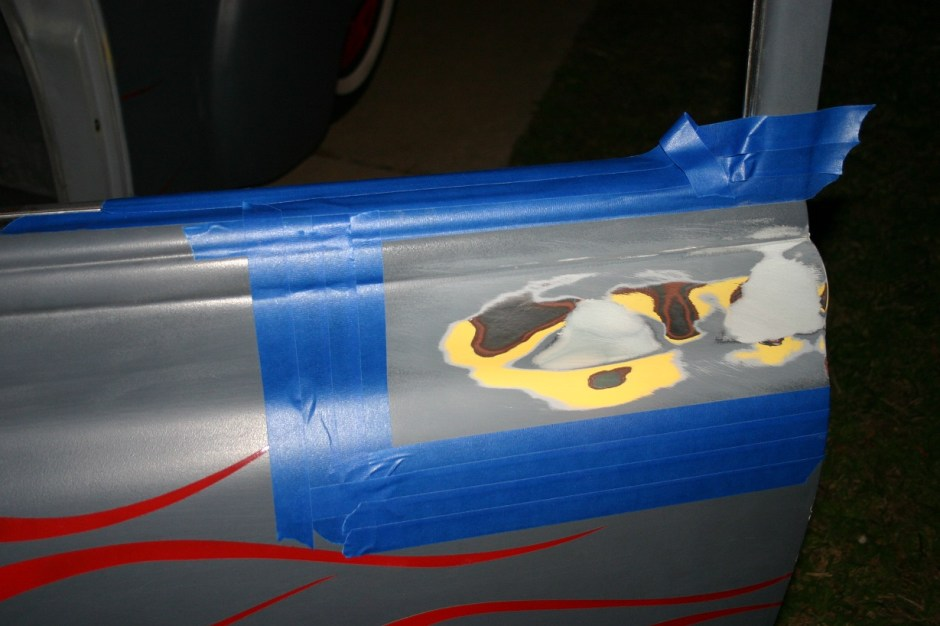 18. Once the repair is smooth, tape off the door and spray on some self-etching primer. A rattle-can high-zinc primer will do the trick and keep the rust away.