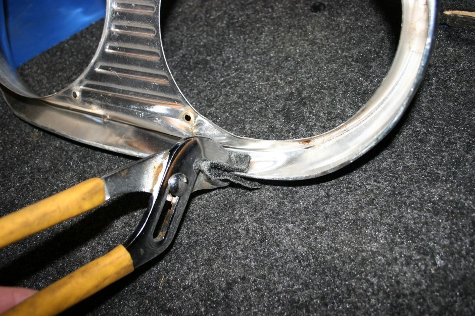 3. The headlight bezel was so badly dented, the hammers needed a better start. A pair of pliers and some scrap carpet is used to tweak the metal back to its original shape.
