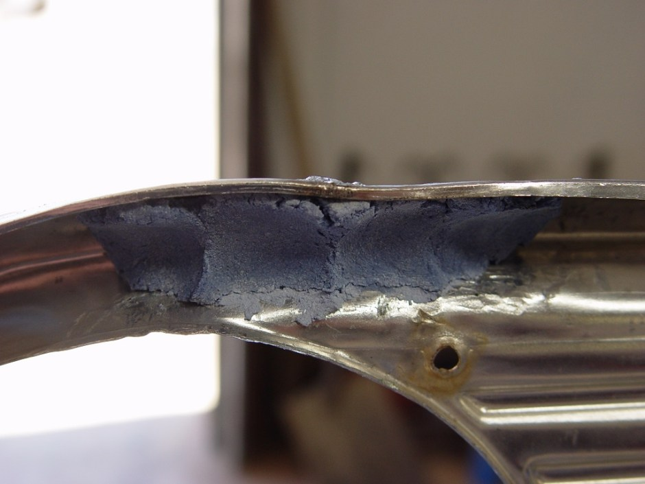 9. Using Eastwood's Anti-Heat compound, the backside of the bezel is filled up. This will help prevent the part from melting during the filling process.
