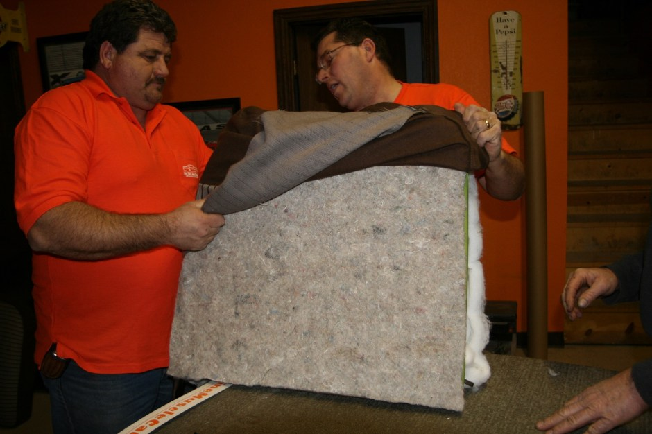 14. Fred and Gary wrapped the Lebarron Bonney seat cover of the frame. We are dealing with fabric, so it stretches more than vinyl, which makes it easier to slide over the seat. If it were vinyl, we would use a small trash bag over the seat, which allows the vinyl to slide.