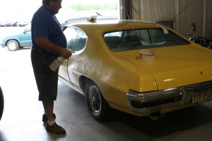 1.The GTO had been washed and wiped down with alcohol before a mixture of soap and water was sprayed on the rear quarter panel. The soapy water deactivates the adhesive for a short time, which allows the stripe to be positioned on the car.