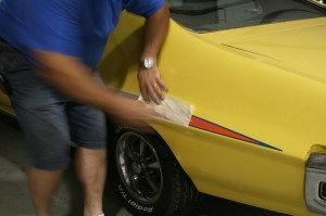 5.Fred Murfin, of Redline Auto Sports, slowly peeled off the paper backing. Sometimes the end of the decal will peel up with the paper, simply press it back down.
