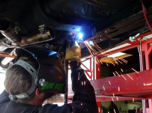 Of course, fire-preventative measures have been taken. Since we can't see what's goin' on inside the car while MIG-welding down below it, Jeremy has pitched his welding blanket tent as we've seen before—just prior to pullin' the trigger.
