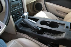 2. First, remove the two screws at the back of the center console lid (under the lid), then gently lift up on the long center console top. It will pop off easily, so don't force it too hard. Once loose, the E-brake handle needs to be lifted up so you can snake the cover off.
