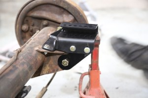 19. The gusset bracket locates the stock lower trailing arm mounting point to the lower shock bracket. This adds rigidity to the system. The bolts are temporarily installed, because the lower trailing arm shares the same fastener.