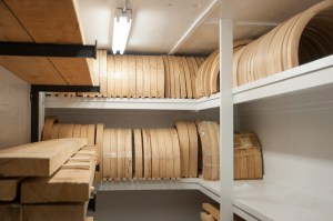Wooden blanks are kept in a climate controlled room to preserve the dryness of the hickory wood. The half circles are blanks for felloes, which is the wooden rim that attaches to the outer steel rim.