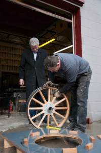 Corky Coker looks on as Jonathan inspects the completed wheel, which is ready to be completed with vintage-style hardware and sent to its customer.