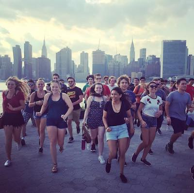 Grupo universitario en Gantry State Park con vistas de skyline de Manhattan