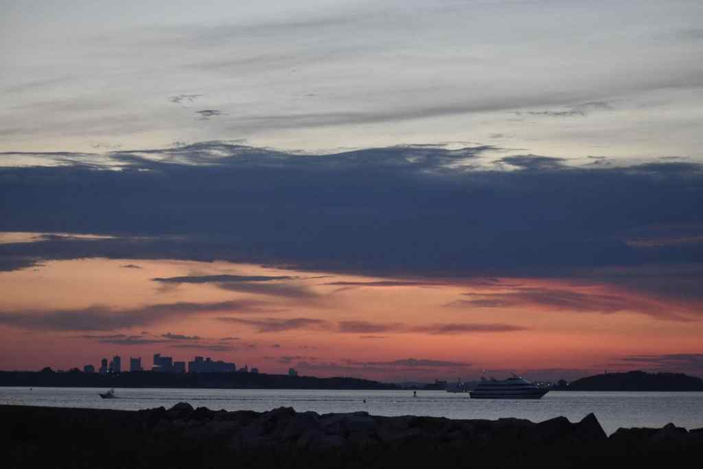 Sunset over Boston Harbor with a cruise ship in the foreground