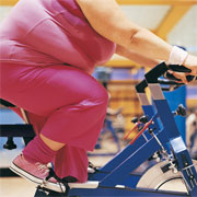 fat woman exercising on stationery bike