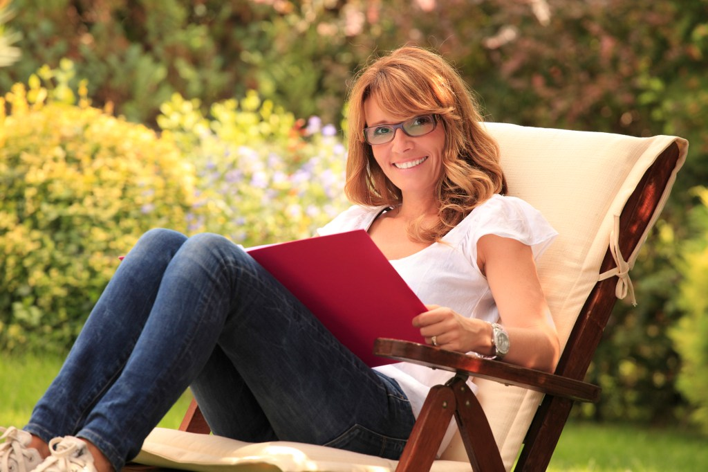 Mature woman sitting in garden and working at home.