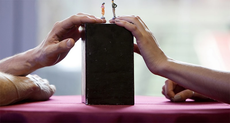 A red tabletop. A black box sits upon it with two hands, each from a different person, resting on the box. On top of a finger from each hand is a model of a person.