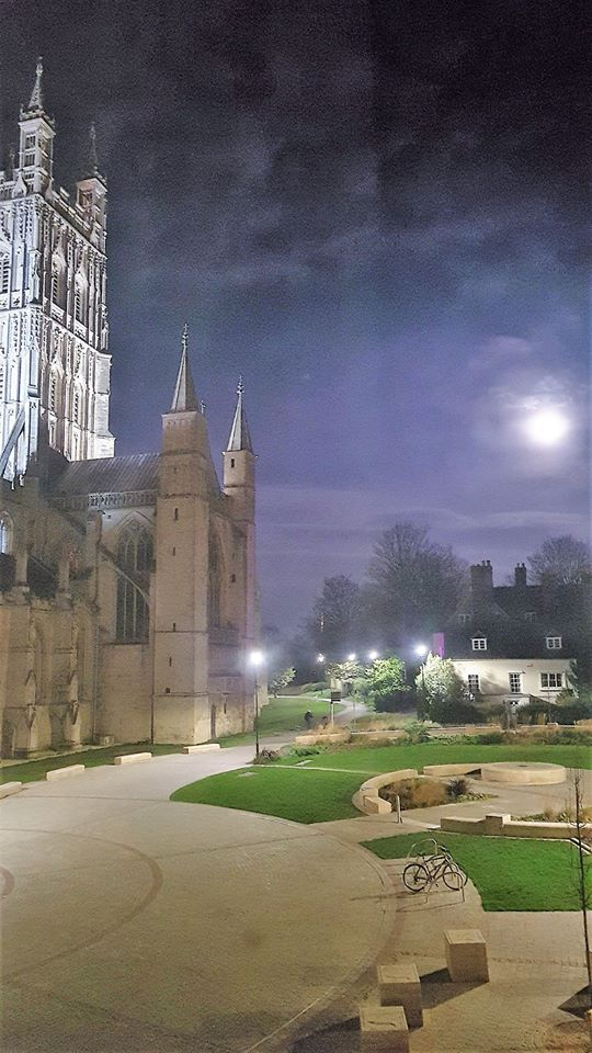 An image taken at night. On the left is the tower of Gloucester's cathedral. In the centre is an empty plaza with one single bicycle stood upon it. The moon rises on the right.