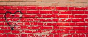 A brick wall. The lower two thirds are painted red and a black heart is spray painted in the left side.