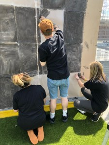 Three people stand and kneel on artificial grass drawing large grey rectangles on a wall.