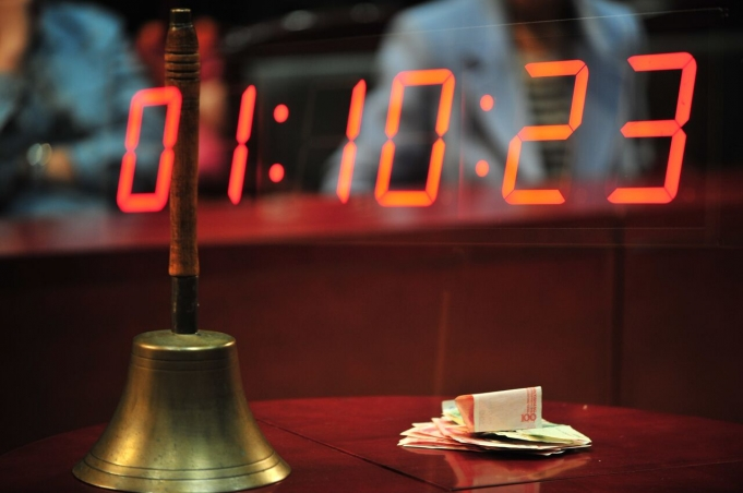 A table top. On it is a bell and a wad of cash. Imposed over it is a digital clock.
