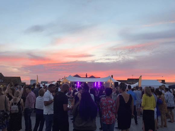 An image taken from rooftop festival. Under the evening sky people mill around in front of a marquee illuminated by the glow of stage lighting.