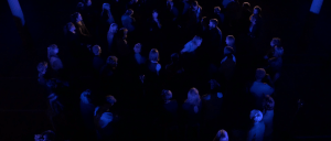 A crowd of people in a dark room illuminated by blue light.