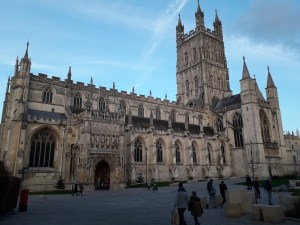 An exterior photo of Gloucester Cathedral. Its imposing shape is against a blue sky. People walk in a plaza in front of it.