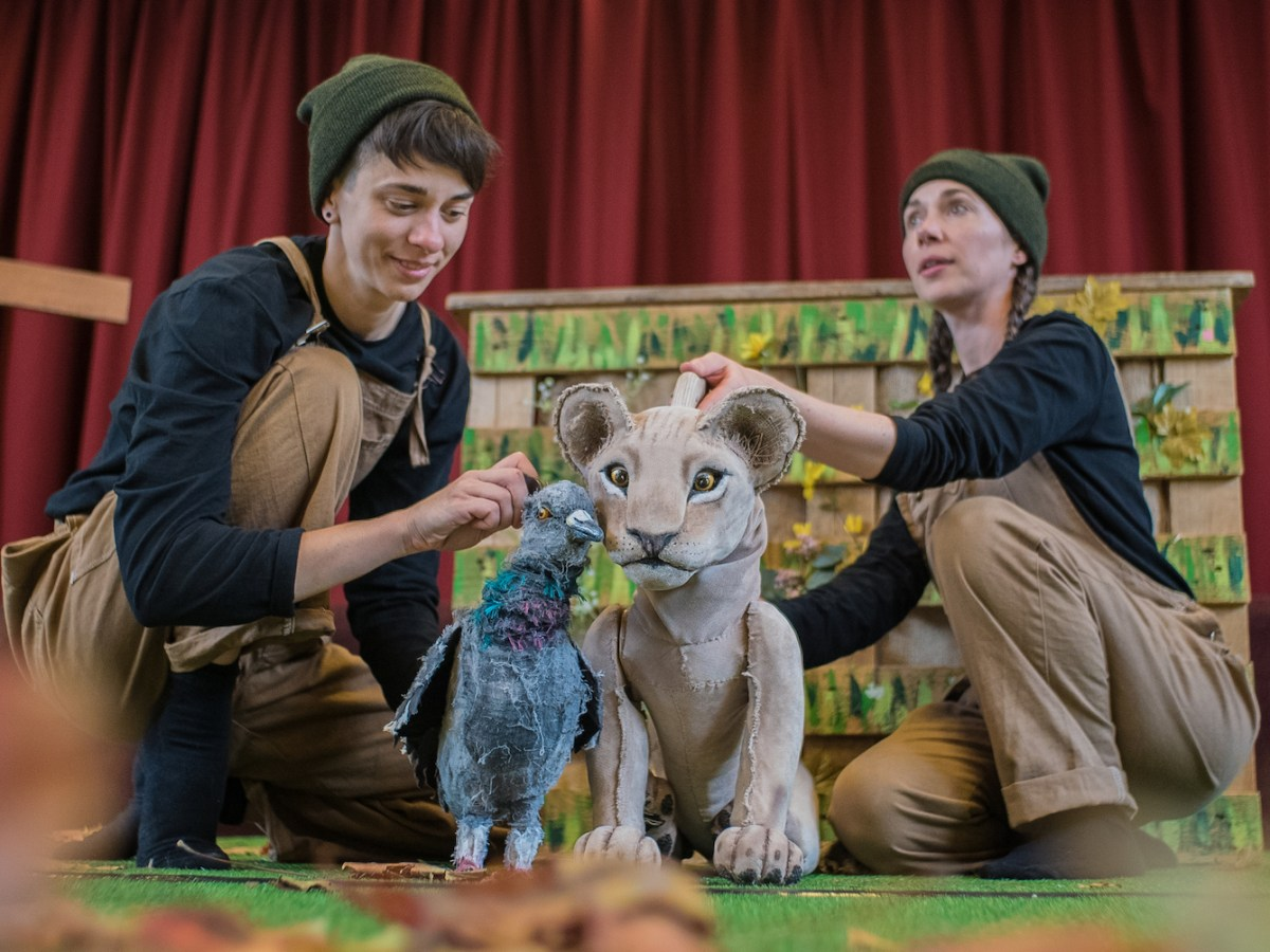 Two actors wearing brown dungarees, black shirts and green hats sit in front of a red curtain. They are puppeteering a pigeon (left) and a lion cub (right)